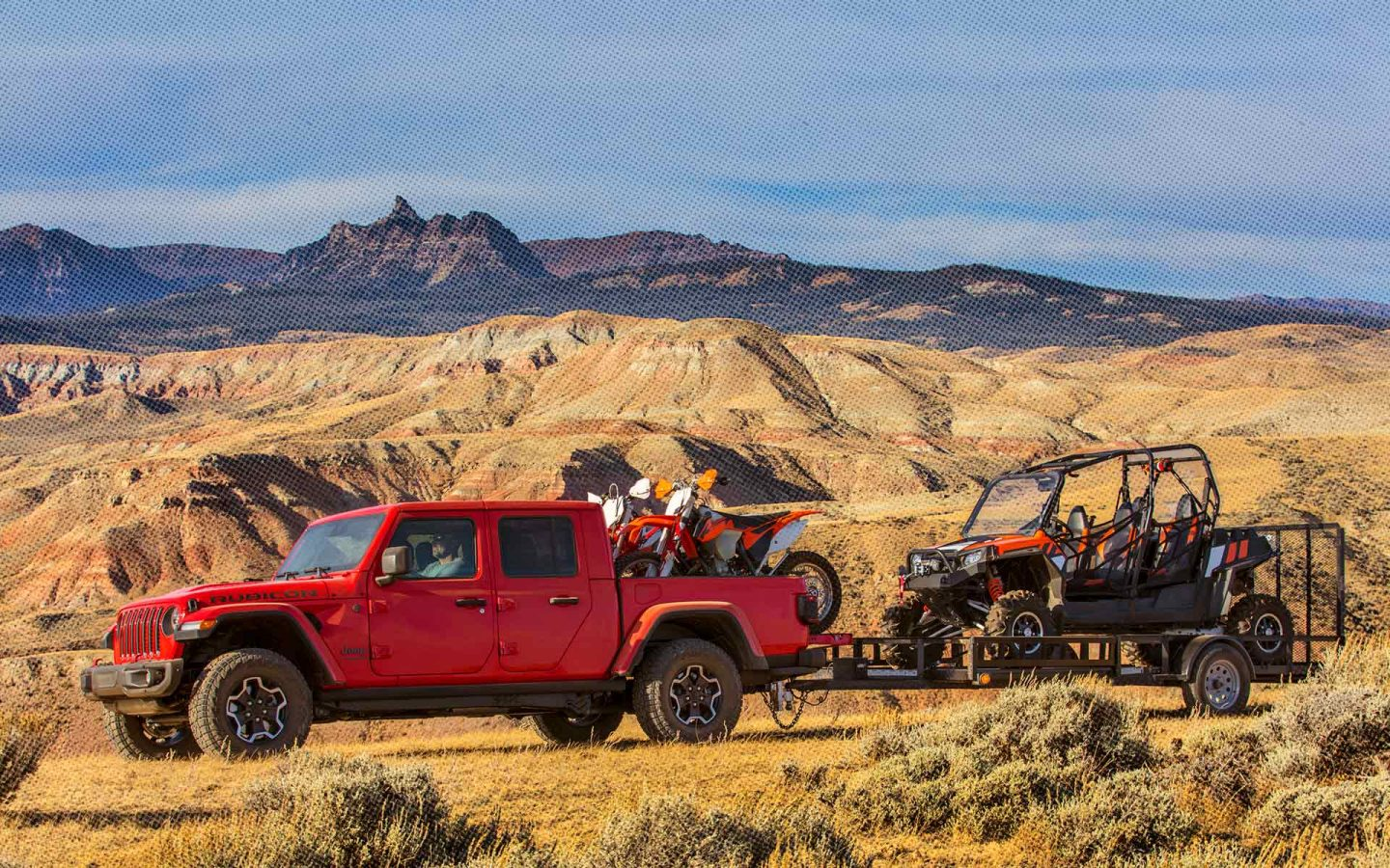 Red Gladiator with dirt bikes in truck bed towing an offroad vehicle