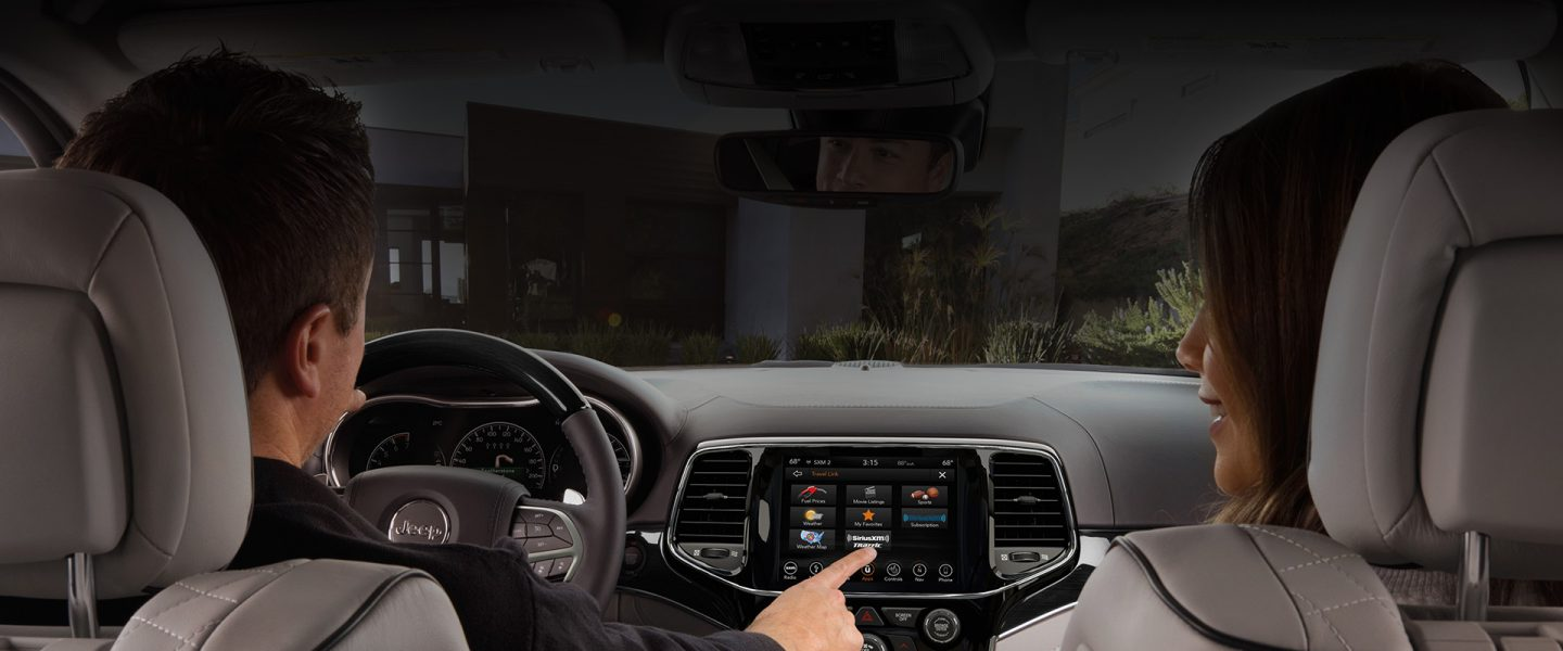 A couple in the front seat of the 2020 Jeep Grand Cherokee as the driver makes a selection on the Uconnect touchscreen.