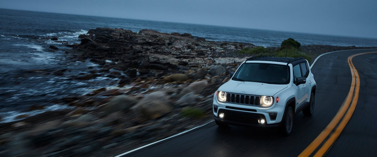 A 2020 Jeep Renegade being driven along a rocky seaside highway at dusk.