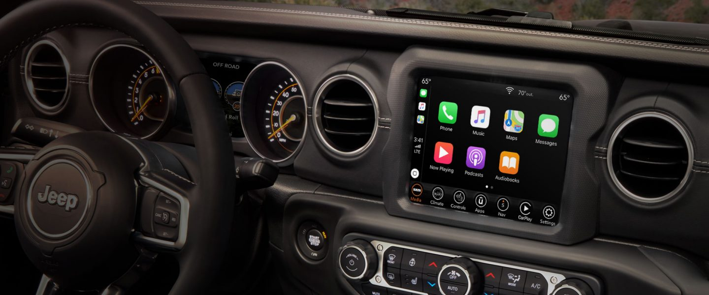 The interior of the 2020 Jeep Wrangler Sahara showing the steering wheel and available 8.4-inch touchscreen.